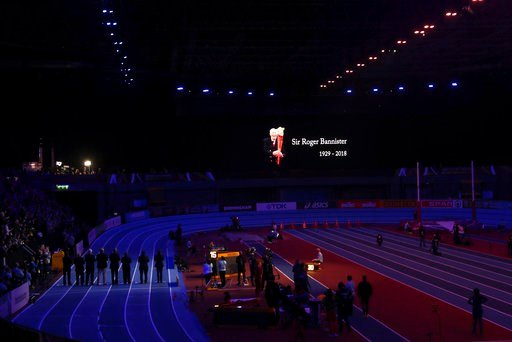 (AP Photo/Alastair Grant). Judges stand on the track to join a minute of silence for late British runner Sir Roger Bannister at the World Athletics Indoor Championships in Birmingham, Britain, Sunday, March 4, 2018.