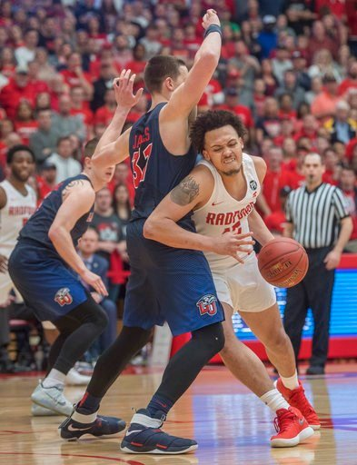 (AP Photo/Don Petersen). Radford forward Devonnte Holland (15) drives against Liberty forward Scottie James (31) during the first half of a Big South Conference championship NCAA college basketball game, Sunday, March 4, 2018, in Radford Va.