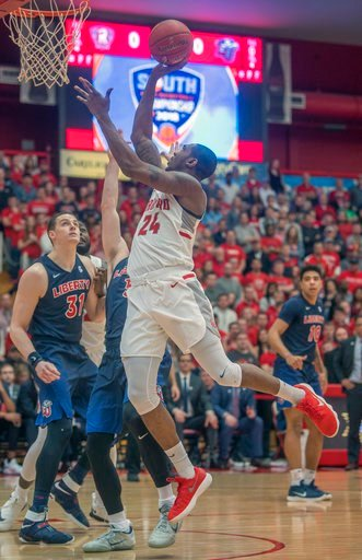 (AP Photo/Don Petersen). Radford forward Ed Polite Jr. (24) shoots over Liberty forward Scottie James (31) during the first half of a Big South Conference championship NCAA college basketball game, Sunday, March 4, 2018, in Radford Va.