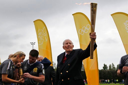 (AP Photo/Lefteris Pitarakis, File). FILE - In this July 10, 2012, file photo, Sir Roger Bannister holds the Olympic Flame on the running track at Iffley Road Stadium in Oxford, England. Bannister, the first runner to break the 4-minute barrier in the ...