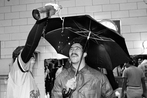 (AP Photo/Tom Lynn, File). FILE - In this Sept. 25, 1983, file photo, Baltimore Orioles pitcher Sammy Stewart, right, uses an umbrella to keep dry as teammate Bill Swaggerty pours a beverage during their victory celebration after defeating the Milwauke...