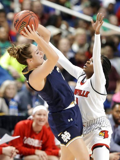 (AP Photo/Chuck Burton). Notre Dame's Marina Mabrey, left, tries to shoot over Louisville's Dana Evans, right, during the first half of an NCAA college basketball game in the championship of the women's Atlantic Coast Conference tournament in Greensbor...