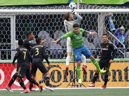 (AP Photo/Ted S. Warren). Seattle Sounders defender Tony Alfaro, second from right, collides with Los Angeles goalkeeper Tyler Miller (1) during the first half of an MLS soccer match, Sunday, March 4, 2018, in Seattle.