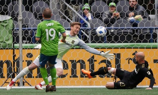 (AP Photo/Ted S. Warren). Los Angeles FC defender Laurent Ciman, right, slides in to help goalkeeper Tyler Miller, center, fend off a shot by Seattle Sounders forward Harry Shipp (19) during the first half of an MLS soccer match, Sunday, March 4, 2018,...