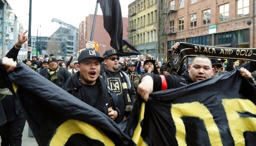 (AP Photo/Ted S. Warren). Members of the District 9 Ultras and other supporters of Los Angeles FC sing and march outside CenturyLink Field before an MLS soccer match against the Seattle Sounders, Sunday, March 4, 2018, in Seattle.