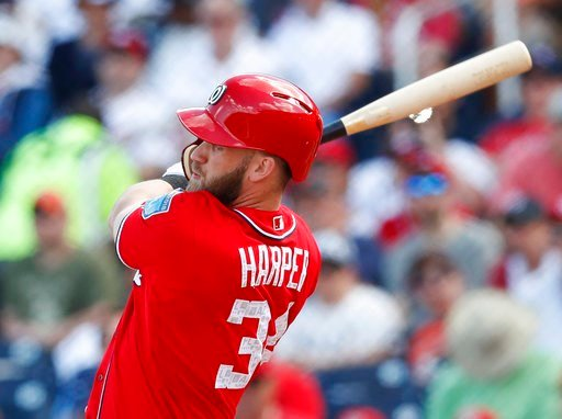 (AP Photo/John Bazemore). Washington Nationals' Bryce Harper (34) follows through on a two-run home run in the third inning of a spring training baseball game against the Detroit Tigers on Sunday, March 4, 2018, in West Palm Beach, Fla.
