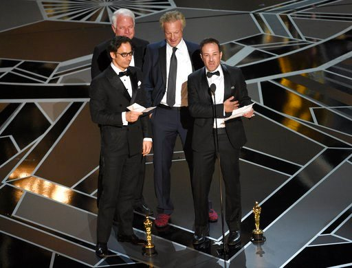 """(Photo by Chris Pizzello/Invision/AP). Dan Cogan, from left, James R. Swartz, David Fialkow, and Bryan Fogel accept the award for best documentary feature for """"Icarus"""" at the Oscars on Sunday, March 4, 2018, at the Dolby Theatre in Los Angeles."""