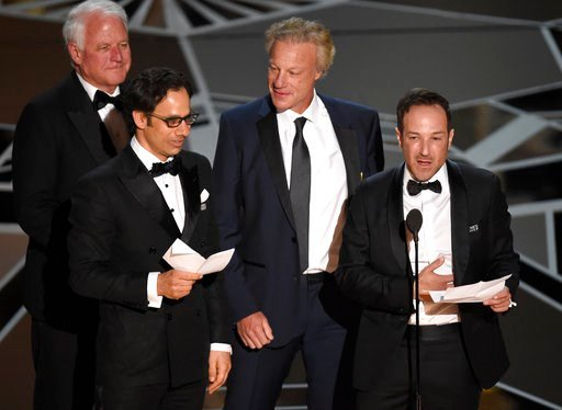 """(Photo by Chris Pizzello/Invision/AP). James R. Swartz, from left, Dan Cogan, David Fialkow, and Bryan Fogel accept the award for best documentary feature for """"Icarus"""" at the Oscars on Sunday, March 4, 2018, at the Dolby Theatre in Los Angeles."""