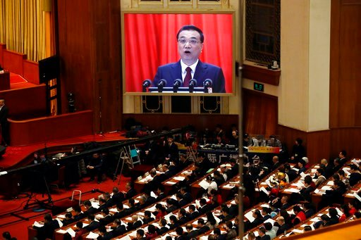 (AP Photo/Ng Han Guan). Chinese Premier Li Keqiang is shown on a large screen as he delivers a work report at the opening session of the annual National People's Congress in Beijing's Great Hall of the People, Monday, March 5, 2018.