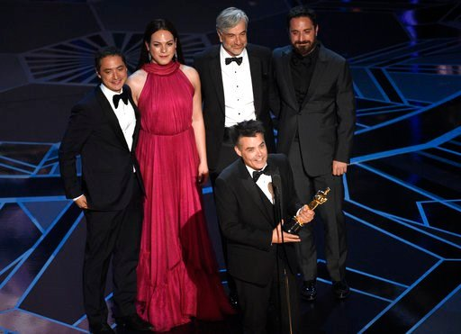 """(Photo by Chris Pizzello/Invision/AP). Sebastian Lelio, foreground center, and Nicolas Saavedra, from back left, Daniela Vega, Alejandro Goic, and Pablo Larrain accept the award for best foreign language film for """"A Fantastic Woman"""" at the Oscars on Su..."""