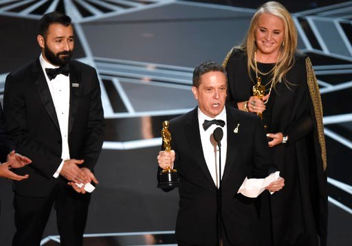 """(Photo by Chris Pizzello/Invision/AP). Adrian Molina, from left, Lee Unkrich, and Darla K. Anderson accept the award for best animated feature film for """"Coco"""" at the Oscars on Sunday, March 4, 2018, at the Dolby Theatre in Los Angeles."""