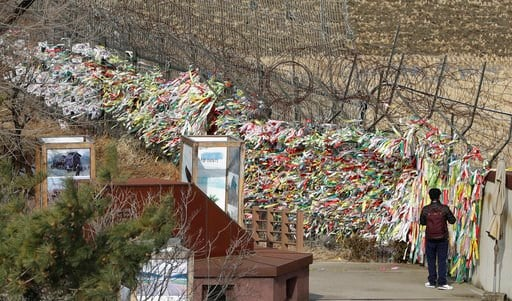 (AP Photo/Lee Jin-man). A man walks near the wire fence decorated with ribbons carrying messages wishing the reunification and peace of the two Koreas at the Imjingak Pavilion in Paju, South Korea, Monday, March 5, 2018.