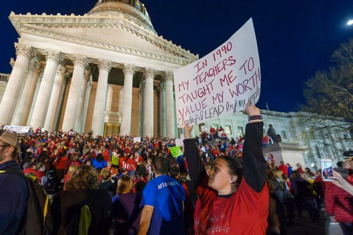 (Craig Hudson/Charleston Gazette-Mail via AP, File). In this Feb. 27, 2018, photo, Jennyerin Steele Staats, a special education teacher from Jackson County, holds her sign aloft outside of the capitol building.