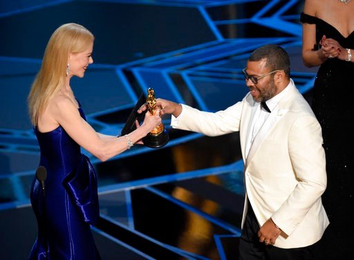 "(Photo by Chris Pizzello/Invision/AP). Nicole Kidman, left, presents Jordan Peele with the award for best original screenplay for ""Get Out"" at the Oscars on Sunday, March 4, 2018, at the Dolby Theatre in Los Angeles."