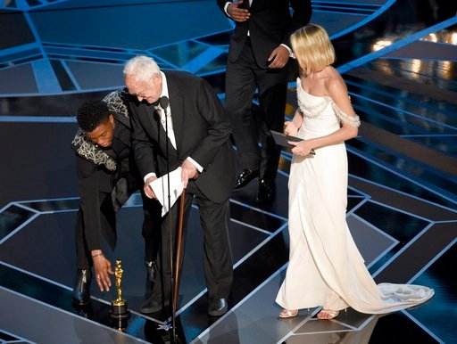 "(Photo by Chris Pizzello/Invision/AP). Chadwick Boseman, left, helps James Ivory, center, pick up his award for best adapted screenplay for ""Call Me by Your Name"" from the stage floor as Margot Robbie looks on at the Oscars on Sunday, March 4, 2018."
