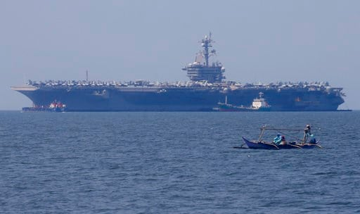 (AP Photo/Bullit Marquez, File). In this Feb. 17, 2018, file photo, fishermen on board a small boat pass by the USS Carl Vinson aircraft carrier at anchor off Manila, Philippines, for a five-day port call.