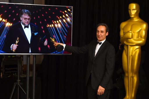 """(Photo by Jordan Strauss/Invision/AP). Alexandre Desplat, winner of the award for best original score for """"The Shape of Water"""", poses in the press room as Guillermo del Toro wins the award for best director for """"The Shape of Water"""" at the Oscars on Sun..."""