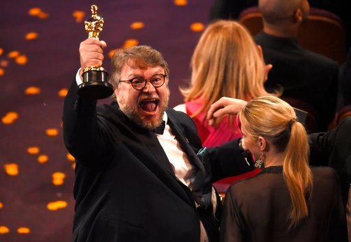 """(Photo by Chris Pizzello/Invision/AP). Guillermo del Toro, winner of the award for best director for """"The Shape of Water"""" celebrates in the audience at the Oscars on Sunday, March 4, 2018, at the Dolby Theatre in Los Angeles."""