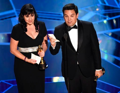 """(Photo by Chris Pizzello/Invision/AP). Kristen Anderson-Lopez, left, and Robert Lopez accept the award for best original song for """"Remember Me"""" from """"Coco"""" at the Oscars on Sunday, March 4, 2018, at the Dolby Theatre in Los Angeles."""