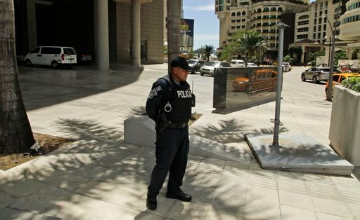 (AP Photo/Arnulfo Franco). FILE - In this Feb. 27, 2018 file photo, a police officer stands outside the Trump Ocean Club International Hotel and Tower in Panama City. The hotel remains open for business against a backdrop of service interruptions, bad ...