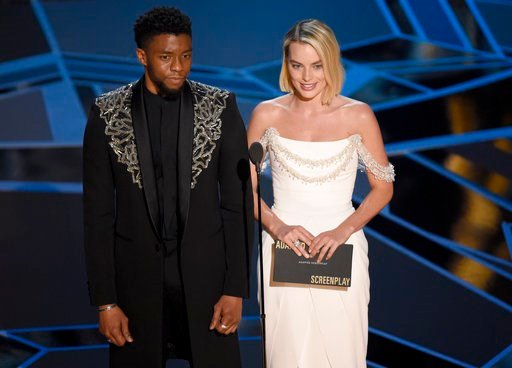 (Photo by Chris Pizzello/Invision/AP). Chadwick Boseman, left, and Margot Robbie present the award for best adapted screenplay at the Oscars on Sunday, March 4, 2018, at the Dolby Theatre in Los Angeles.