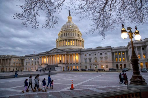 (AP Photo/J. Scott Applewhite). FILE - In this Jan. 21, 2018 file photo, people walk by the U.S. Capitol on the second day of the federal shutdown as lawmakers negotiate behind closed doors in Washington.  After last year's big win on taxes, Republican...