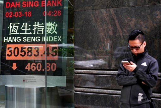 (AP Photo/Vincent Yu). A man stands next to an electronic board showing Hong Kong share index outside a local bank in Hong Kong, Monday, March 5, 2018. Asian shares fell in early trading Monday as investors evaluated the uncertain results of Italian el...