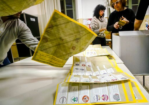 (Giuseppe Lami/ANSA via AP). Scrutineers count votes in a polling station in Rome, Sunday, March 4, 2018, at the end of Italy's election day.