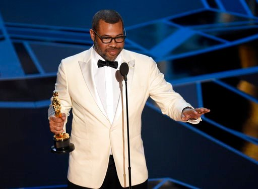 "(Photo by Chris Pizzello/Invision/AP). Jordan Peele accepts the award for best original screenplay for ""Get Out"" at the Oscars on Sunday, March 4, 2018, at the Dolby Theatre in Los Angeles."