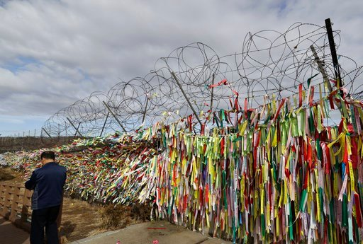 (AP Photo/Lee Jin-man). A man walks near the wire fence decorated with ribbons carrying messages wishing the reunification and peace of the two Koreas at the Imjingak Pavilion in Paju, South Korea, Monday, March 5, 2018. South Korea's president will se...