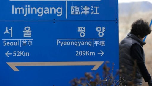 (AP Photo/Lee Jin-man). A woman walks by a signboard showing the distance to North Korea's capital Pyongyang and to South Korea's capital Seoul from Imjingang Station in Paju, South Korea, Monday, March 5, 2018. South Korea's president will send a dele...