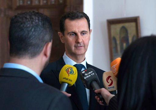 (Syrian Presidency Facebook Page via AP). This photo provided by the official Facebook page of the Syrian Presidency, Syrian President Bashar Assad, center, speaks with reporters, in Damascus, Syria, Sunday, March 4, 2018 . Assad vowed Sunday to contin...