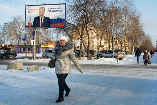 "(AP Photo/Nataliya Vasilyeva). In this photo taken on Tuesday, Feb. 13, 2018, a woman walks past a campaign billboard with the picture of President Vladimir Putin that reads: ""March 18, 2018. A Strong President for a Strong Russia"", in Nizhny Tagil, Ru..."