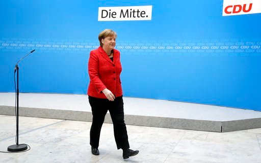 (AP Photo/Michael Sohn). German Chancellor and chairwomen of the German Christian Democratic Union (CDU), Angela Merkel, leaves after a statement at the party headquarters in Berlin, Germany, Monday, March 5, 2018.