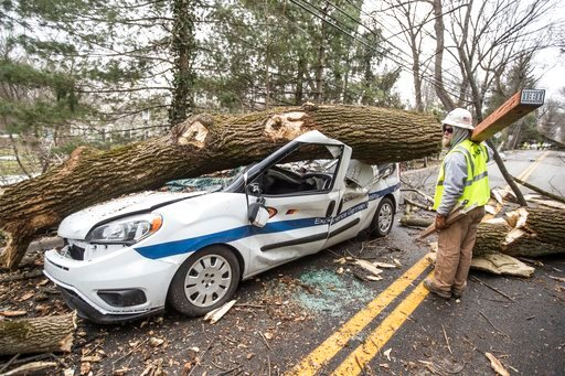 (Michael Bryant/The Philadelphia Inquirer via AP). An electrical worker for INTREN, a electric company from Chicago that drove two days to get to Philadelphia to help PECO restore power, walks by a damaged vehicle on  in Bryn Mawr, Pa., on Sunday, Marc...