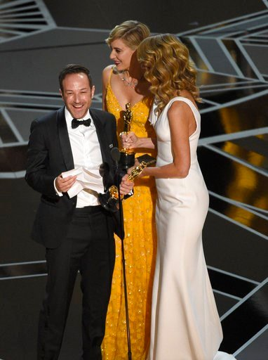 """(Photo by Chris Pizzello/Invision/AP). Laura Dern, from right, and Greta Gerwig present Bryan Fogel with the award for best documentary feature for """"Icarus"""" at the Oscars on Sunday, March 4, 2018, at the Dolby Theatre in Los Angeles."""