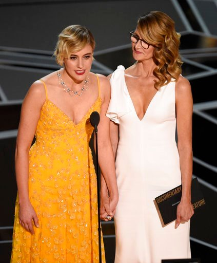 (Photo by Chris Pizzello/Invision/AP). Greta Gerwig, left, and Laura Dern present the award for best documentary feature at the Oscars on Sunday, March 4, 2018, at the Dolby Theatre in Los Angeles.