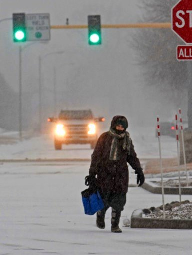 (Tom Stromme/The Bismarck Tribune via AP). A pedestrian makes her way in Bismarck, N.D., Monday, March 5, 2018, as snow falls. Freezing rain, heavy snow and strong winds are blowing into the northern Plains, impacting travel, schools and government off...