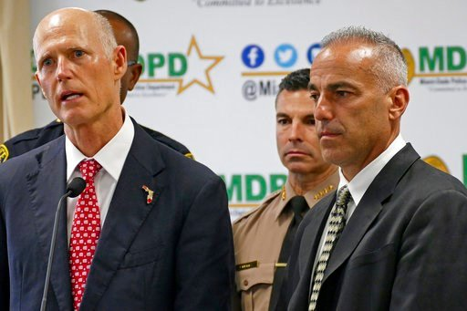 (C.M. Guerrero/Miami Herald via AP, File). FILE- In this Feb. 27, 2018 file photo, Florida Gov. Rick Scott talks alongside Andrew Pollack, right, whose daughter Meadow was murdered in Parkland during press conference at Miami-Dade Police Department in ...