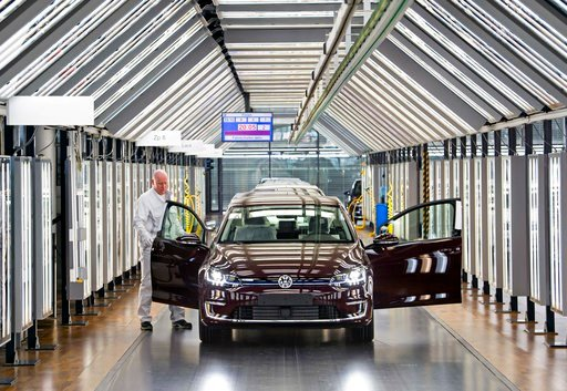 (AP Photo/Jens Meyer). Roland Schulz makes the final check of an e-Golf electric car in the so-called light tunnel in the German car manufacturer Volkswagen's Transparent Factory in Dresden, Germany, Monday, March 5, 2018.