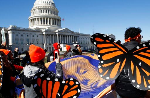 "(AP Photo/Jacquelyn Martin). Wearing ""butterfly wings,"" supporters of the Deferred Action for Childhood Arrivals (DACA) program hold a tarp with an image of President Donald Trump as they march in support of DACA, Monday, March 5, 2018, on Capitol Hill..."