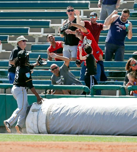 (AP Photo/John Raoux). A fan with a glove catches a foul ball in front of Pittsburgh Pirates first baseman Josh Bell, left, during the second inning of a spring baseball exhibition game against the Atlanta Braves, Monday, March 5, 2018, in Kissimmee, F...