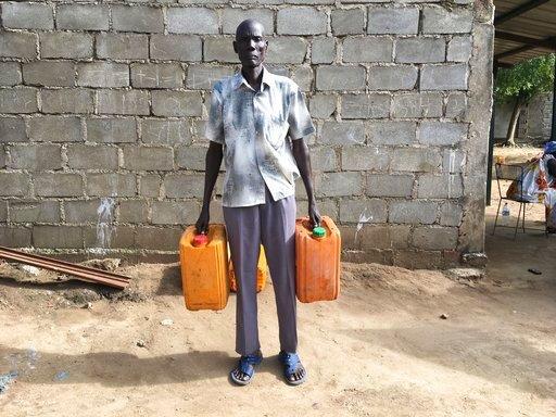"(AP Photo/Sam Mednick, File). FILE - In this Monday, Oct. 2, 2017 file photo, black market fuel trader Nyuol Deng holds empty jerrycans outside his house. South Sudan's state-owned oil company has been ""captured by predatory elites"" and is being used t..."
