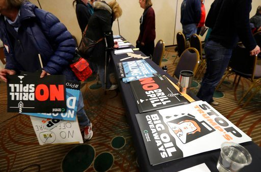 (AP Photo/Ted S. Warren). Signs opposing offshore oil drilling are distributed, Monday, March 5, 2018, at a hearing in Olympia, Wash., organized by a coalition of environmental groups opposed to the Trump administration's proposal to expand offshore oi...