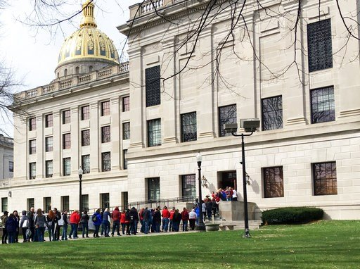 (AP Photo/John Raby). Striking West Virginia teachers line up to enter the state Capitol on Monday, March 5, 2018, in Charleston, W.Va.