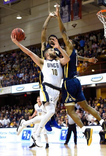 (AP Photo/Kathy Kmonicek). UNC-Greensboro guard Francis Alonso (10) drives the ball to the basket against East Tennessee State guard Desonta Bradford (1) and forward David Burrell (2) in the first half of an NCAA college basketball game for the Souther...