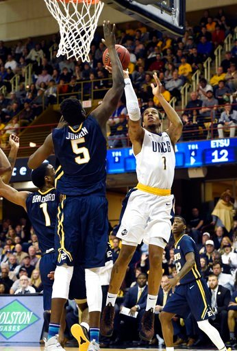 (AP Photo/Kathy Kmonicek). UNC-Greensboro forward Marvin Smith (1) shoots over East Tennessee State center Peter Jurkin (5) in the first half of an NCAA college basketball game for the Southern Conference tournament championship on Monday, March 5, 201...