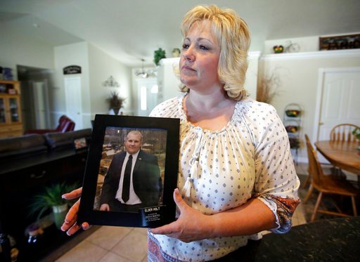 (AP Photo/Rick Bowmer, File). FILE - In this July 13, 2016 file photo, Laurie Holt holds a photograph of her son Joshua Holt at her home, in Riverton, Utah. A secret backchannel has opened up in 2018, between normally hostile Venezuelan and U.S. offici...