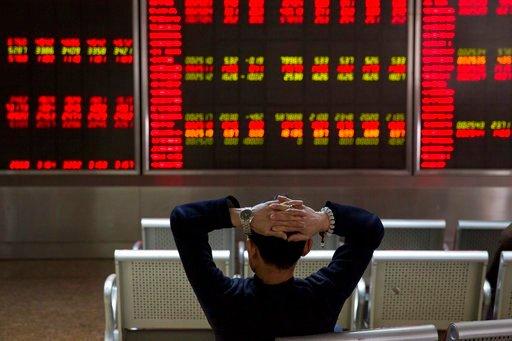 (AP Photo/Ng Han Guan). A Chinese man monitors stock prices at a brokerage in Beijing, Tuesday, March 6, 2018. Asian stock markets surged Tuesday despite U.S.-Chinese trade tensions after Wall Street posted its strongest gains in a week.