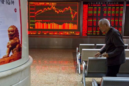 (AP Photo/Ng Han Guan). An elderly Chinese man walks past stock market prices displayed at a brokerage in Beijing, Tuesday, March 6, 2018. Asian stock markets surged Tuesday despite U.S.-Chinese trade tensions after Wall Street posted its strongest gai...